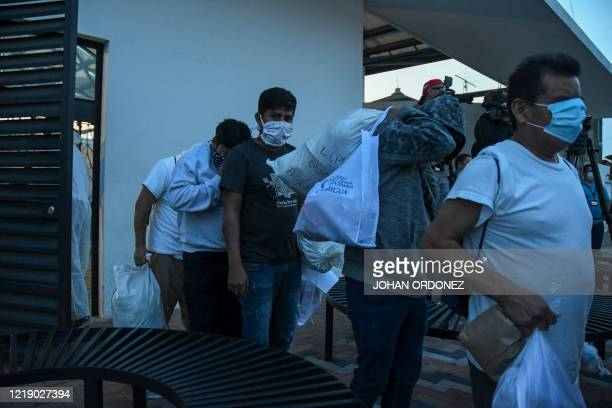 Migrants part of a group of 50 Guatemalans deported from the United States wear face masks as a preventive measure against the novel coronavirus...