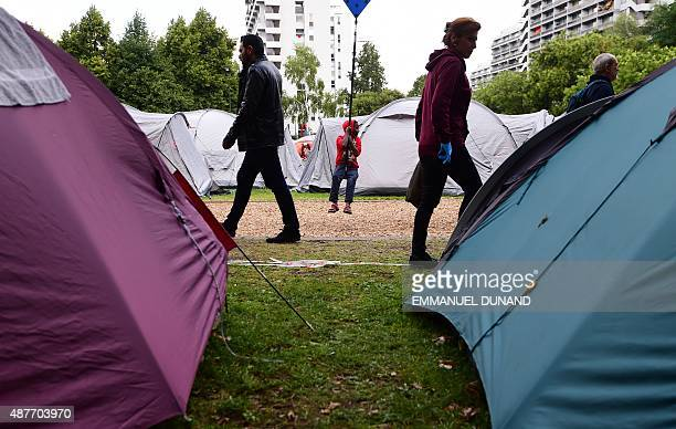 Migrants pass through a makeshift tent camp in a park in Brussels on September 9 as they wait to have their asylum claims processed The camp is...