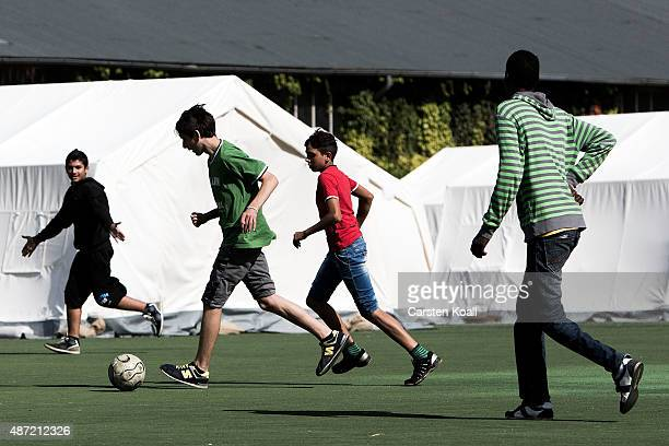 Migrants play soccer at a shortterm housing facility for arriving migrants and refugees in Spandau district on September 7 2015 in Berlin Germany...