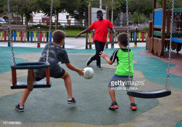 A migrants plays football with children outside the migrants reception center in the Spanish Basque city of Irun on August 9 2018 With migrant...