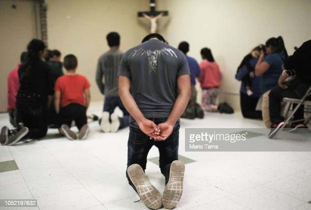 Migrants pray at an Annunciation House shelter for migrants on October 13 2018 in El Paso Texas Annuciation House said it is currently receiving over...