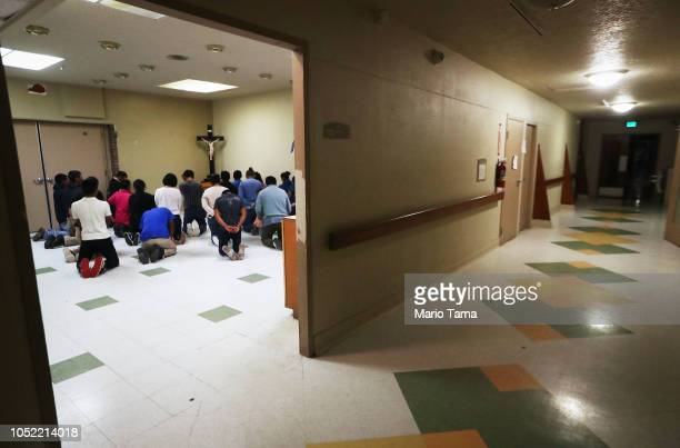Migrants pray at an Annunciation House shelter on October 13 2018 in El Paso Texas Annunciation House said it is currently receiving over 700...