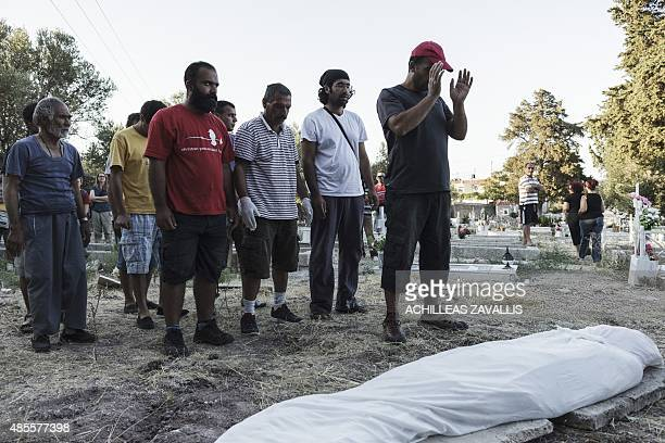 Migrants pray over the dead body of an unidentified refugee from Syria found off the Greek coast by the Greek Coast Guard in the cemetery of Agios...