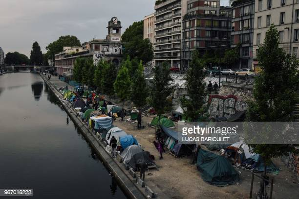 Migrants prepare their belongings prior to the evacuation by police of their makeshift camp along the Canal de SaintMartin at Quai de Valmy in Paris...