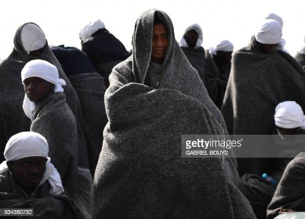 TOPSHOT Migrants protect themselves from the cold with blankets as they wait to arrive in the port of Cagliari Sardinia on May 26 2016 aboard the...