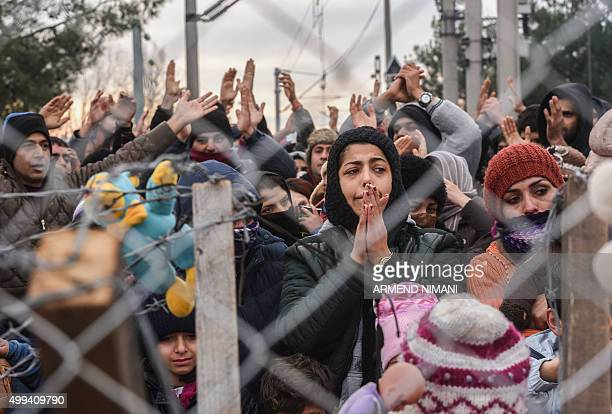 Migrants protest behind a fence against restrictions limiting passage at the GreekMacedonian border near Gevgelija on December 1 2015 Since last week...