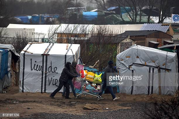 Migrants push belongings away in a shopping trolley as police and demolition workers clear the 'jungle' migrant camp on March 01 2016 in Calais...