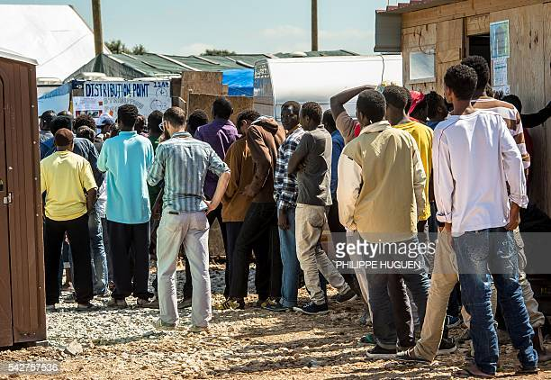Migrants queue at a distribution point inside the 'Jungle' camp for migrants and refugees in Calais on June 24 the day after Britain voted to leave...