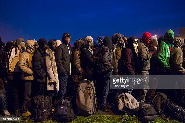 Migrants queue at a reception point outside the Jungle migrant camp before boarding buses to refugee centres around France on October 24 2016 in...