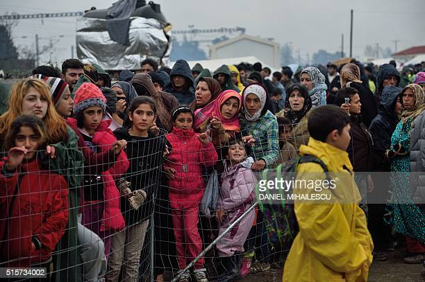 Migrants queue for food at a makeshift camp at the GreekMacedonian border near the Greek village of Idomeni on March 15 where thousands of refugees...