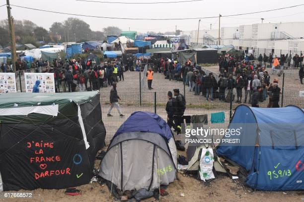 TOPSHOT Migrants queue outside a hangar where they will be sorted into groups and put on buses for shelters across France as part of the full...