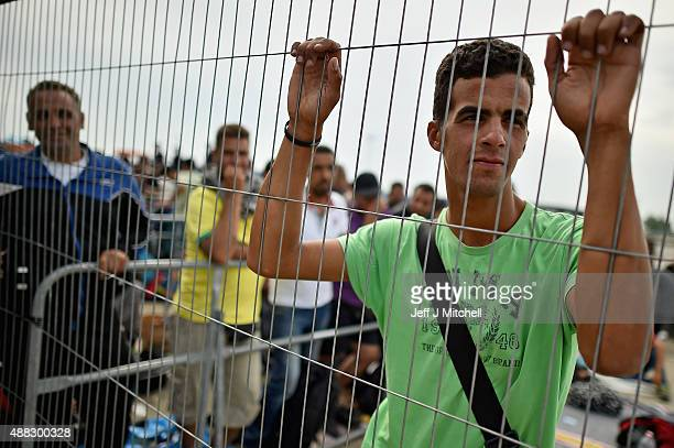 Migrants queue to board buses bound for Vienna from Hegyshalom holding centre on the Austrian border after Hungarian authorities closed the open...