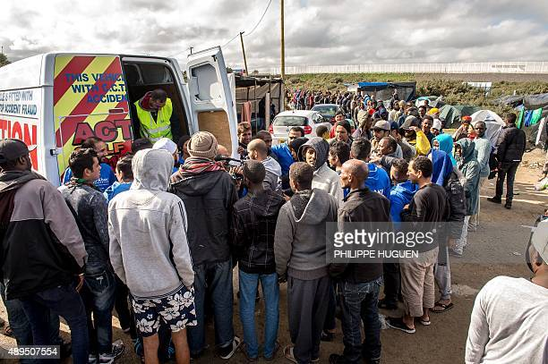 Migrants queue to get food at a site dubbed the 'New Jungle' where some 3000 people have set up camp most seeking desperately to get to England in...