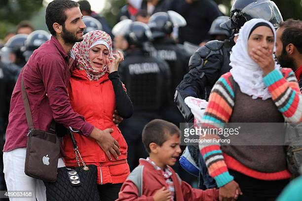 Migrants react after being allowed through the Slovenian police line in the small Croatian village of Harmica on September 19, 2015 in Harmica,...