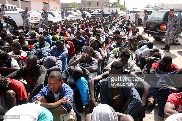 Migrants rescued by the Libyan coastguard at sea sit in a naval base near the capital Tripoli on October 8 2015 Libyan authorities said almost 300...