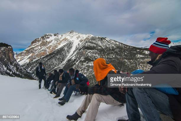 Migrants rest after crossing the French border on December 22 2017 in Bardonecchia Turin Italy After the police reinforced the Frejus and and...