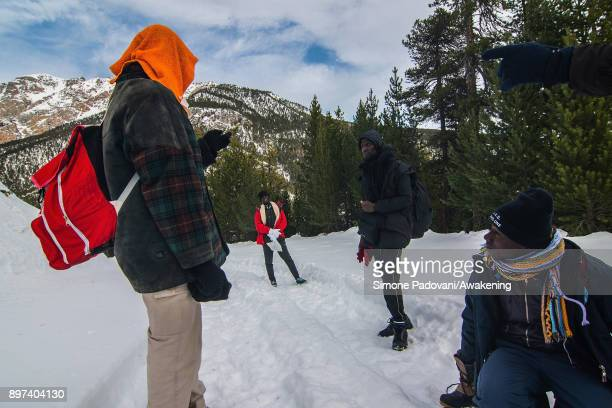 Migrants rest and speak after crossing the French border on December 22 2017 in Bardonecchia Turin Italy After the police reinforced the Frejus and...