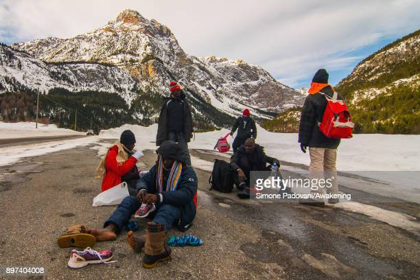 Migrants rest before starting to cross Colle della Scala during another attempt to reach the French border on December 22 2017 in Bardonecchia Turin...
