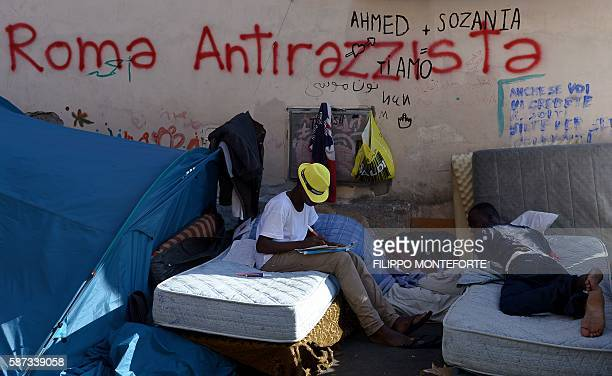 Migrants rest by a graffiti reading 'Rome antiracist' in the street of Via Cupa outside the former Baobab migrant reception centre next to the...