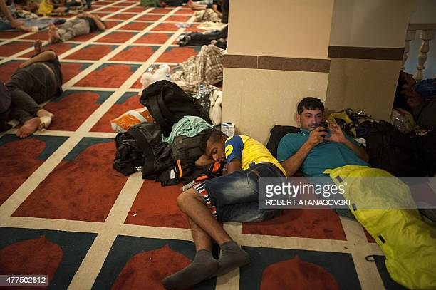 Migrants rest in a Macedonian mosque in Kumanovo 10 kilometers from the Serbian border on June 17 2015 Migrants from impoverished and wartorn...