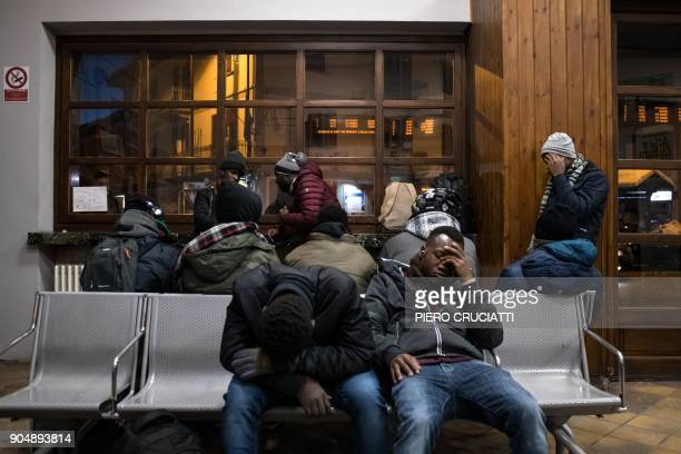 Migrants rest in the waiting hall of the train station in Bardonecchia Italy on January 13 2018 Migrants are now trying to reach France crossing the...