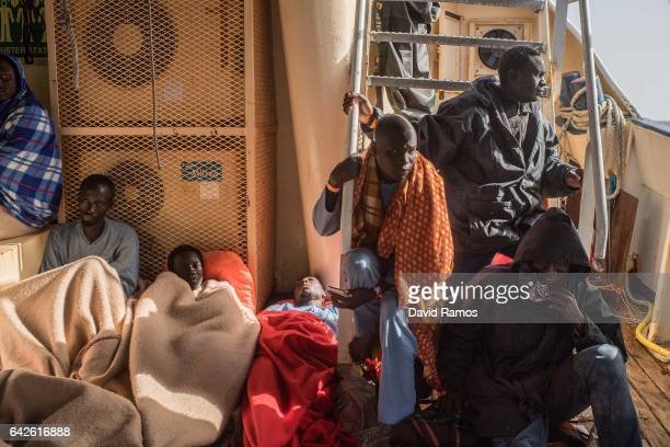 Migrants rest on the deck of the Spanish NGO Proactiva Open Arms rescue vessel Golfo Azzurro after being rescued by the Italian Coast Guard at 24...