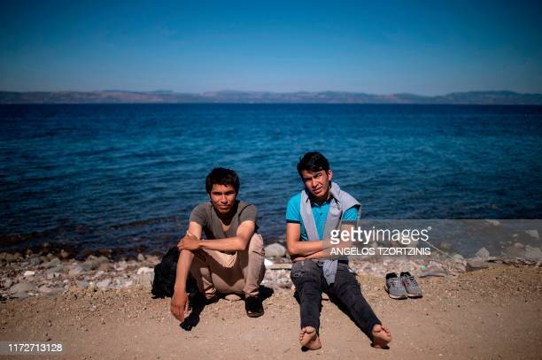 Migrants rest on the Greek Mediterranean island of Lesbos on October 1 after crossing the Aegean Sea from Turkey in a dinghy