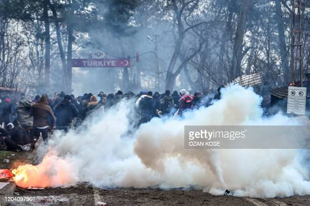 Migrants run away as Greek anti riot police officers use tears gas on the buffer zone Turkey-Greece border, at Pazarkule, in Edirne district, on...