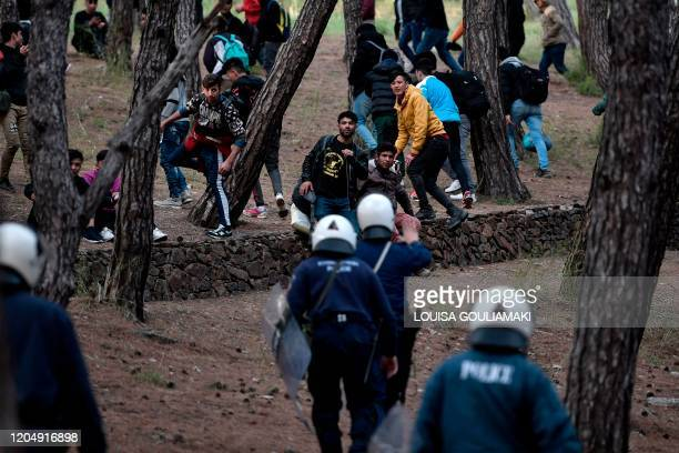 TOPSHOT Migrants run from riot police after being pushed to go back to Moria camp from the port of Mytilene on the island of Lesbos where they were...
