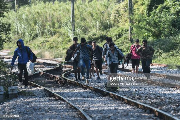 Migrants run to cross a railway near Idomeni at the border between Greece and North Macedonia on July 16, 2020. - Four years after the evacuation of...