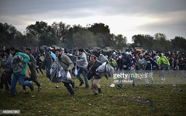 Migrants run towards the village of Rigonce, after crossing over from Croatia on October 23, 2015 in Rigonce, Slovenia. Thousands of migrants marched...