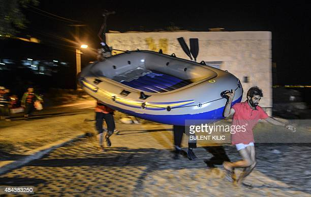 Migrants run with their boat to reach the Greek island of Kos on early August 18 2015 off the shore of Bodrum southwest Turkey Authorities on the...