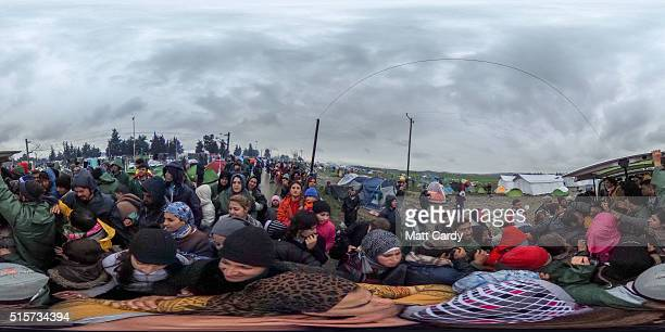 Migrants scramble for shoes been given out by a charity from the back of a van at the Idomeni refugee camp is seen on March 15 2016 in Idomeni Greece...