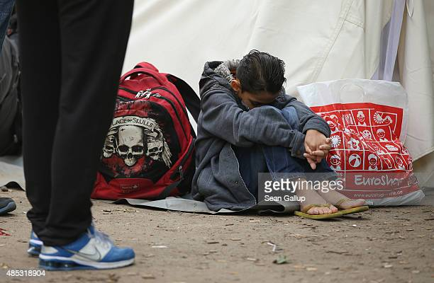 Migrants seeking asylum in Germany wait outside the Central Registration Office for Asylum Seekers of the State Office for Health and Social Services...