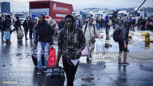 Migrants seen moving with their luggages during their arrival at the port 400 migrants and refugees were transferred upon their arrival from the...