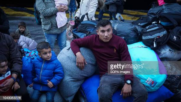 Migrants seen sited on their luggages during their arrival at the port 400 migrants and refugees were transferred upon their arrival from the island...