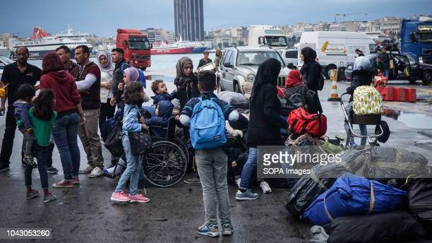 Migrants seen standing with their luggages during their arrival at the port 400 migrants and refugees were transferred upon their arrival from the...