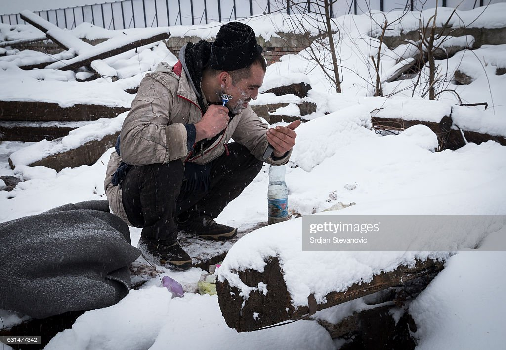 A migrants shaves surrounded by snow outside a derelict customs warehouse on January 11, 2017 in Belgrade, Serbia. It is estimated that around 1, 000 migrants are sleeping rough in Serbia, enduring temperatures as low as 20 degrees celcius.