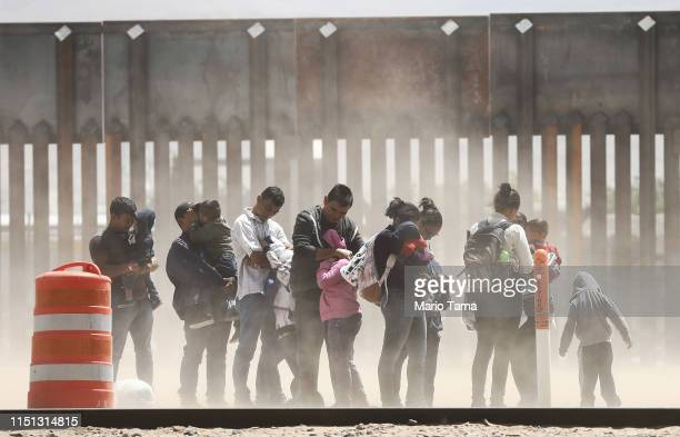 Migrants shield themselves from blowing dust while being detained after crossing to the US side of the USMexico border barrier on May 17 2019 in El...