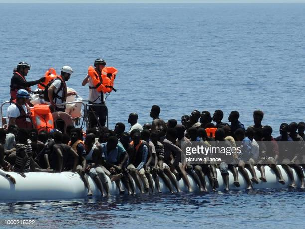 Migrants sit aboard an overcrowded rubber dinghy in the Mediterranean 27 June 2017 Helpers of the aid organisation Doctors without Borders and SOS...