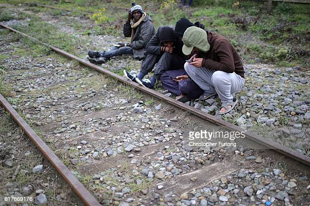 Migrants sit along a railway track as they begin to leave the Jungle camp before authorities demolish the site on October 24 2016 in Calais France...