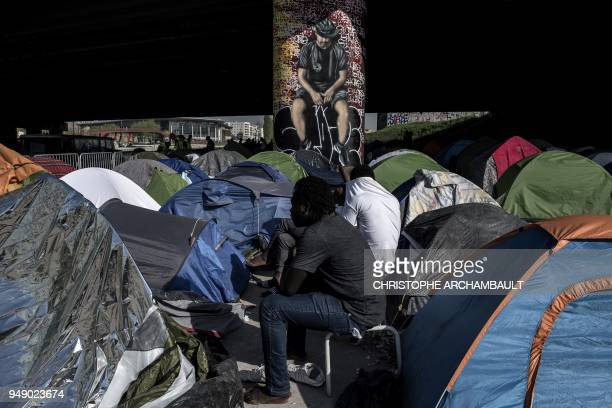 TOPSHOT Migrants sit by tents at a makeshift camp set under a bridge near Porte de la Villette northern Paris on April 20 2018