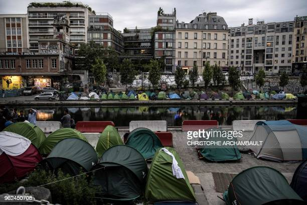 TOPSHOT Migrants sit by their tents at a makeshift camp along the canal SaintMartin in Paris on May 25 2018