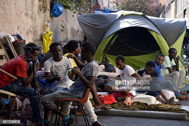 Migrants sit in the street of Via Cupa just outside the former Baobab migrants reception centre next to the Tiburtina train station in Rome on August...