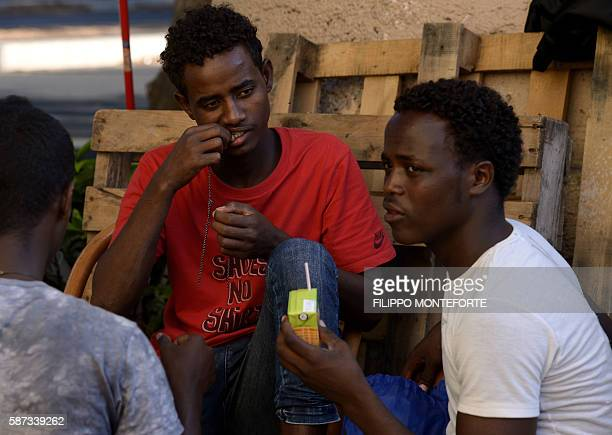 Migrants sit in the street of Via Cupa outside the former Baobab migrants reception centre next to the Tiburtina train station in Rome on August 8...
