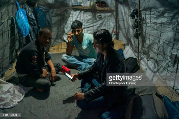Migrants sit in their tents in an olive grove that has become a makeshift camp next to the overcrowded Moria Refugee Camp on October 17 2019 in...
