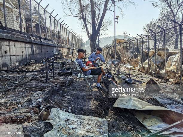 Migrants sit inside the burnt Moria Camp on the Greek island of Lesbos on September 9 after a major fire. - Thousands of asylum seekers on the Greek...