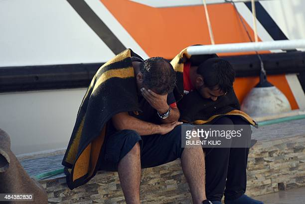 Migrants sit on a harbor after been rescued by Turkish coast guard from a sinking ship trying to reach the Greek island of Kos on August 18 in Bodrum...
