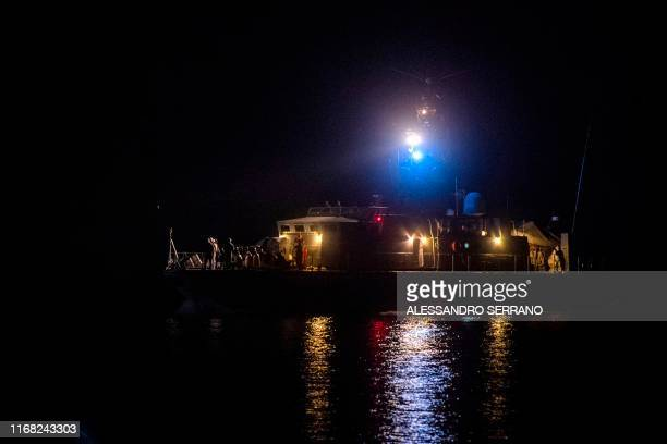 Migrants sit on an Italian coast guard ship after disembarking from the Ocean Viking ship rescue ship off Italy's southern island of Lampedusa in the...