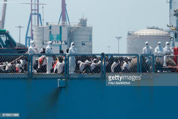 TOPSHOT Migrants sit on the deck of the Italian navy ship Orione as the ship enters the port of Valencia on June 17 2018 The Aquarius rescue ship...